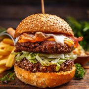 Delicious burgers with beef patty, bacon, cheese and cabbage on rustic wooden background